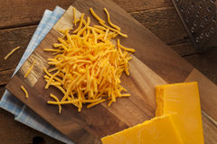 Organic Shredded Sharp Cheddar Cheese. On a Cutting Board royalty free stock image