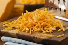 Organic Shredded Sharp Cheddar Cheese. On a Cutting Board royalty free stock photography