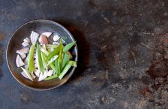 Sliced green onion and shallots in a gray bowl, left of center, on a gray background, top view stock photo