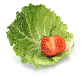 Organic Sliced Tomato on Cabbage. Fresh red organic tomato on green cabbage leaf on white background Stock Photos
