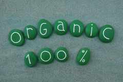 Organic one hundred percent text with green stones. Organic slogan for one hundred percent quality with green painted stones over green sand Vector Illustration