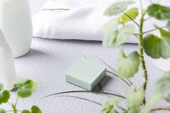 Organic soap at the bathroom.Bar of green herbal soap on the grey surface on the bathroom counter. Bar soaps and dried plant on the dark surface, top view royalty free stock photos