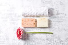 Organic Soaps with Herbs and Flowers, cotton Towel and Gerbera Daisy. Copy space. Horizontal Stock Photo