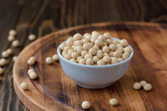 Organic soybeans at white ceramic bowl over wooden table. Stock Images