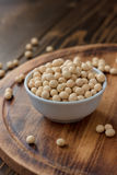 Organic soybeans at white ceramic bowl over wooden table. Royalty Free Stock Image
