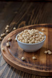 Organic soybeans at white ceramic bowl over wooden table. Royalty Free Stock Photo