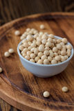 Organic soybeans at white ceramic bowl over wooden table. Stock Photo