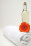 Organic Spa Treatment. Organic massage oil and gerbera flower on crisp white bath towel for luxury relaxing treatment Stock Images
