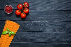 Organic spaghetti with fresh cherries, red pepper in little glas. S bowl and basil leaf on black wooden background. Italian cuisine, free copy space. Food Royalty Free Stock Images