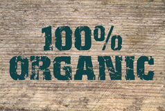 100% Organic  stamped text on old plank Royalty Free Stock Images