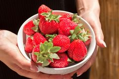 Organic strawberries in bowl in hands. Fresh and healthy food Stock Photography