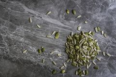 Organic Sunflower and Pumpkin seeds on a marble kitchen worktop background royalty free stock image