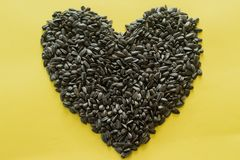 Organic Sunflower seed in Heart Shape.  on Yellow Background. Closeup, Top view. stock photos