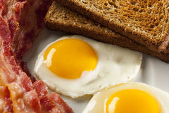 Organic Sunnyside up Egg with toast and bacon Royalty Free Stock Photos