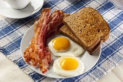Organic Sunnyside up Egg with toast and bacon Stock Photos
