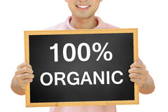 100% ORGANIC text on blackboard held by smiling man Stock Photography