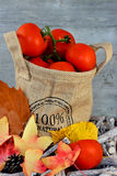 Organic tomatoes in a jute bag with autumn leaves Stock Images