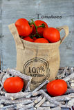 Organic tomatoes in a jute bag with autumn leaves Royalty Free Stock Images