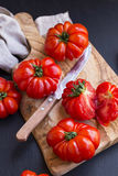 Organic tomatoes on wooden cutting board Stock Photo
