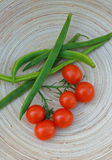Organic tomatos and beans. Freshly picked organic cherry tomatoes on the vine, with freshly picked green beans, set on a wooden oval platter Royalty Free Stock Photography