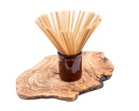 Organic uncooked Brown Rice Spaghetti pasta arranged in a tall round brown ceramic jar on a natural olive wood cutting board. Gluten-free and sodium-free royalty free stock image
