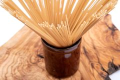 Organic uncooked Brown Rice Spaghetti pasta arranged in a tall round brown ceramic jar on a natural olive wood cutting board. Gluten-free and sodium-free stock images