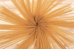 Organic uncooked Brown Rice Spaghetti pasta arranged in a tall round brown ceramic jar on a natural olive wood cutting board. Gluten-free and sodium-free royalty free stock photo
