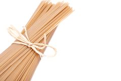 Organic uncooked Brown Rice Spaghetti pasta tied with a straw isolated on white background. Gluten-free and sodium-free. Alternative to traditional pastas royalty free stock photo