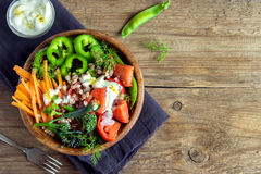Organic vegetable salad. Fresh organic vegetable salad with buckwheat over rustic wooden background with copy space Stock Images