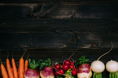 Organic vegetables background. Fresh harvested vegetables on the dark wooden background, top view, with copy space Stock Image