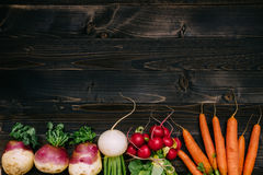 Organic vegetables background. Fresh harvested vegetables on the dark wooden background, top view, with copy space.  Royalty Free Stock Photo