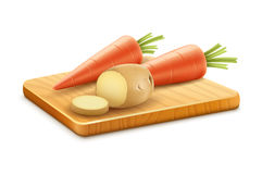 Organic vegetables carrots potatoes cut on wooden board Royalty Free Stock Image