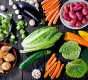 Organic vegetables on dark wooden board. Stock Image