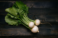 Organic vegetables. Fresh harvested turnip on the dark wooden background, top view.  Royalty Free Stock Images