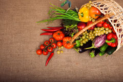 Organic vegetables, fruits and lettuce in wicker basket on kitch Royalty Free Stock Images