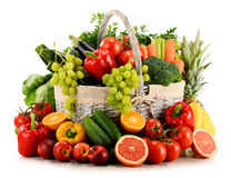 Organic vegetables and fruits in wicker basket on white. Variety of organic vegetables and fruits in wicker basket on white Royalty Free Stock Photos