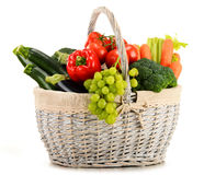 Organic vegetables and fruits in wicker basket on white Stock Photos
