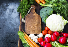 Organic vegetables harvest frame.Wooden board with fresh bio veg. Organic vegetables  harvest with wooden board, cauliflower, broccoli, greens, tomatoes Royalty Free Stock Photo