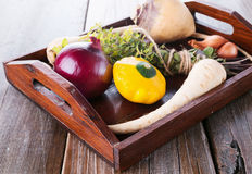 Organic vegetables and herbs on wooden tray. Colorful organic healthy vegetables on wooden tray on a rustic wooden background stock photos