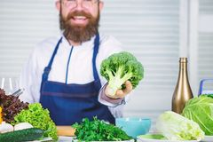 Organic vegetables. I choose only healthy ingredients. Man cook hat and apron hold broccoli. Healthy nutrition concept. Bearded professional chef cooking royalty free stock image