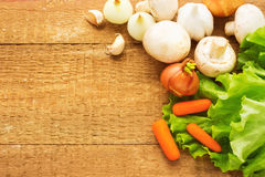 Organic vegetables on wooden background. Onion, champignons, car Stock Photo