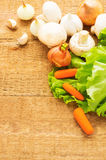 Organic vegetables on wooden background. Onion, champignons, car Stock Photos