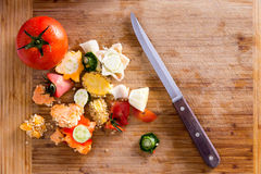 Organic Wastes on Wooden Chopping Board with Knife Royalty Free Stock Photos