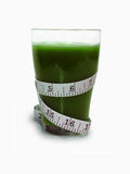 Organic Spirulina Green Smoothie. Measuring tape wrapped around a gross thick green spirulina smoothie Stock Image