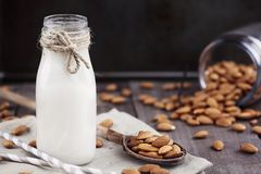 Fresh Almond Milk with Fresh Almonds. Organic white almond milk in a glass bottle with whole almonds spilled over a rustic wooden table Royalty Free Stock Image
