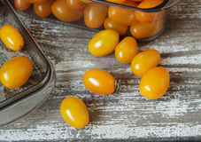 Organic yellow cherry tomatoes in plastic container Stock Images