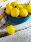 Organic yellow cherry tomatoes with water drops in blue bowl Stock Images