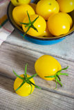 Organic yellow cherry tomatoes with water drops in blue bowl Stock Photo