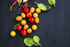 Organic yellow and red cherry tomatoes with spinach and spices Royalty Free Stock Images