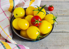 Organic yellow red cherry tomatoes with water drops in blue bowl Stock Photography